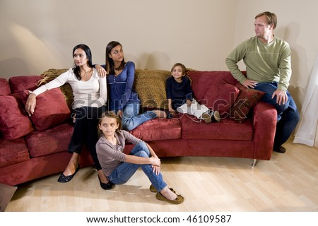 Portrait of family sitting on couch with father and teen daughter having disagreement