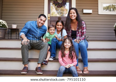 Portrait Of Family Sitting On Steps in Front Of House