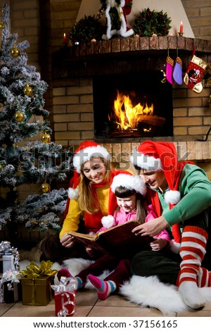 Portrait of family spending Christmas evening at reading book by fireplace