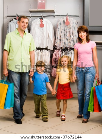 Portrait of family walking down shopping mall after good shopping