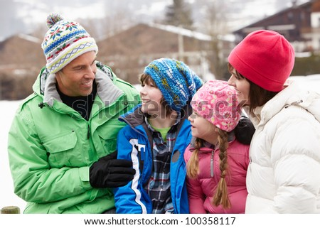 Portrait Of Family Wearing Winter Clothes In Snowy Landscape - stock photo
