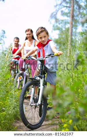 Portrait of family with one boy riding bikes