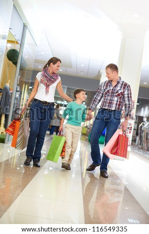 Portrait of family with paperbags walking in the mall