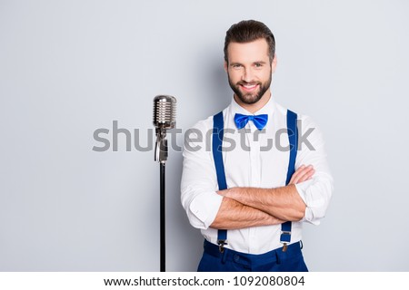 Portrait of famous joyful singer with bristle, wearing blue pants bowtie suspenders shirt, having his arms crossed, standing near mic isolated on grey background #1092080804