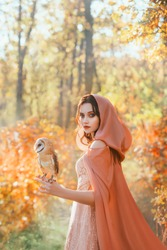 Portrait of fantasy girl princess walks with white bird barn owl on her hand. Beautiful mystical woman in medieval cape cloak with hood looks into camera. Background bright autumn nature, forest trees