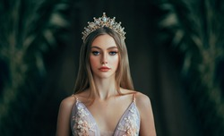 Portrait of fantasy medieval girl princess in dark gothic room. Woman queen looking at camera, beauty face. Vintage trendy glamour dress golden luxury crown, long loose blonde hair. Fashion model.