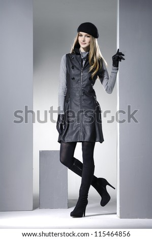 Portrait of fashion model in fashion clothes posing with cube light background
