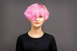 Portrait of fashion model young woman with stylish dyed pink hair in black clothes on dark background