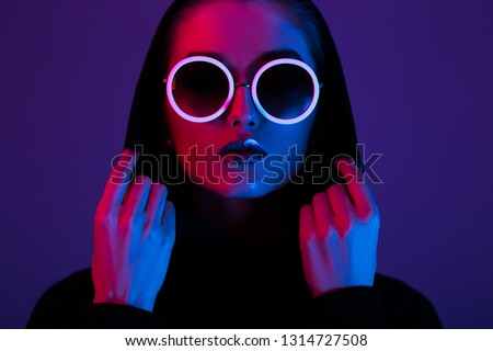 Portrait of fashion young girl in a black sweater with a hood and round sunglasses in red and blue neon light in the studio #1314727508