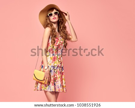 Portrait of Fashion Young woman in Floral Dress. Pretty Girl in Hat, Sunglasses. Female model in Stylish Summer Outfit. Vanilla Color. Beautiful Lady on Pink. Vintage #1038551926
