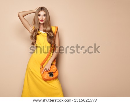 Portrait of Fashion Young woman in Yellow Dress. Female Model in Stylish Spring Summer Outfit. Girl Posing on a Beige Background. Stylish Hairstyle. Blonde Lady with Orange Handbag