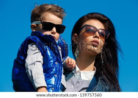 Portrait of fashionable baby boy and his gorgeous mother (hollywood star) in trendy sunglasses walking in the street. Sunny spring day. Outdoor shot
