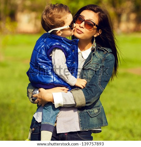 Portrait of fashionable baby boy and his gorgeous mother (hollywood star) in trendy sunglasses walking in the street. Kid kissing mom. Sunny spring day. Outdoor shot
