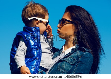 Portrait of fashionable baby boy and his gorgeous mother (hollywood star) in trendy sunglasses walking in the street. Son is crying. Sunny spring day. Outdoor shot