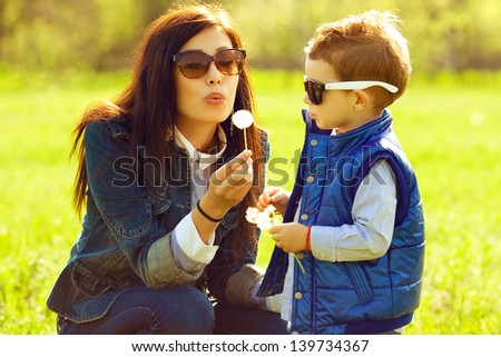 Portrait of fashionable baby boy and his gorgeous mother in trendy sunglasses playing with dandelion in the park. Sunny spring day. Outdoor shot