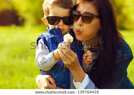 Portrait of fashionable baby boy and his gorgeous mother in trendy sunglasses playing with dandelion in the park. Sunny spring day. Close-up. Copy-space. Outdoor shot