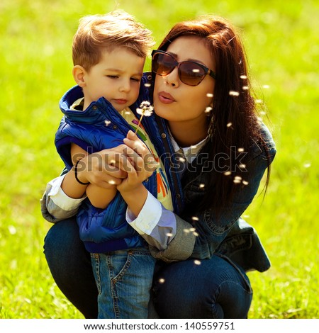 Portrait of fashionable baby boy and his gorgeous mother in trendy sunglasses playing with dandelion in the park. Sunny spring day. Hipster style. Outdoor shot