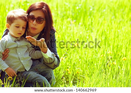 Portrait of fashionable baby boy and his gorgeous mother in trendy sunglasses playing with dandelion in the park. Sunny spring day. Hipster style. Copy-space. Outdoor shot