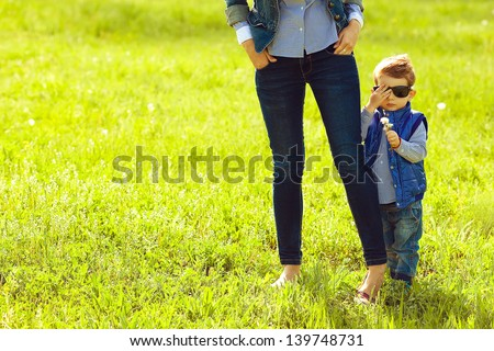 Portrait of fashionable baby boy in trendy sunglasses and his mother standing in the park. Sunny spring day. Hipster style. Copy-space. Outdoor shot