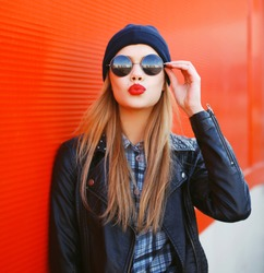 Portrait of fashionable blonde girl with red lipstick blowing lips air kiss wearing a rock black style outdoors in the city
