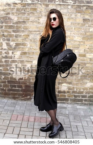 Portrait of fashionable blonde girl with red lipstick wearing a rock black style outdoors in the city #546808405