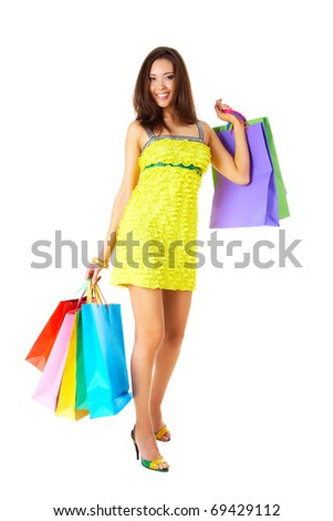 Portrait of fashionable female in yellow glamorous dress with colorful paperbags