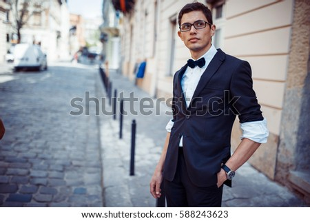 Portrait of fashionable well dressed man posing outdoors looking away #588243623