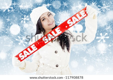 Portrait of fashionable woman showing banner of winter sale. isolated on white background
