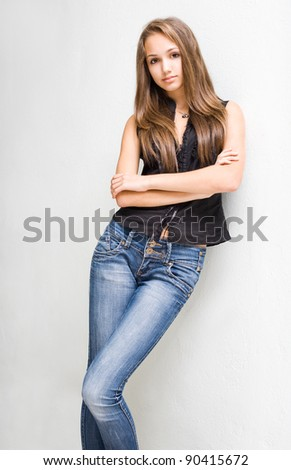 Portrait of fashionable young brunette model in blue jeans and black top