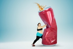 Portrait of fat young woman wearing sportswear while hitting a can of soft drink. Isolated on blue background