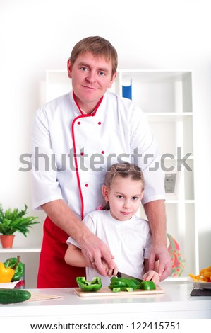 portrait of father and daughter cooking salad together in the kitchen