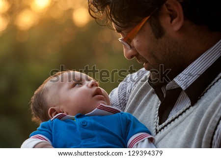 portrait of father and son against nature background, Indian man holding his son in lap.