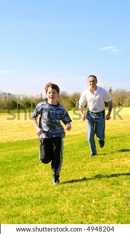 Portrait of father and son playing outdoors - stock photo