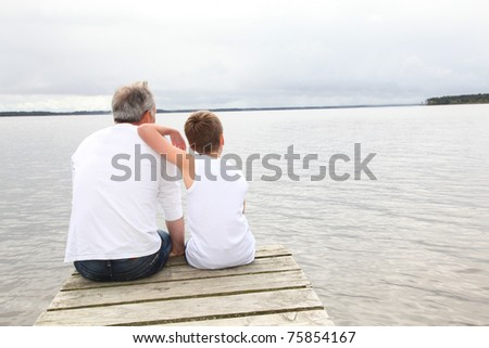 Portrait of father and son sitting on a pontoon