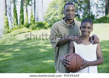 Portrait of father and son with basketball