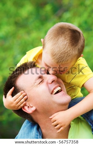 Portrait of father cuddling his son during summer vacation