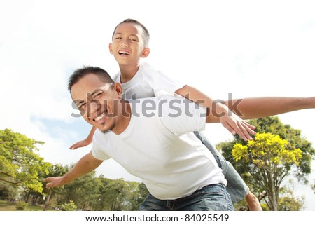 Portrait of father giving his son piggyback ride against sky