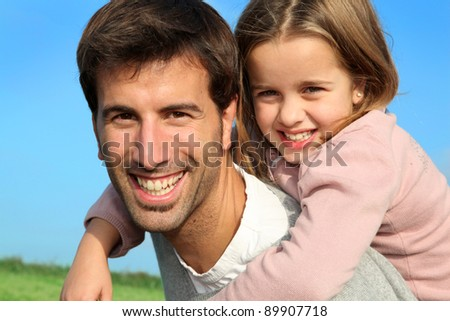 Portrait of father giving piggyback ride to daughter
