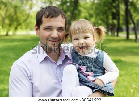Portrait of father with little daughter outdoor in summer park - stock photo