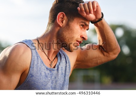 Portrait of fatigued fitness guy on hot sunny day