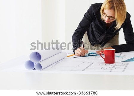 portrait of female architect drawing line on blueprint. Copy space
