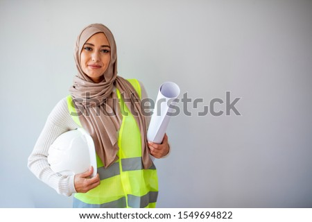 Portrait of female architect in hidjab. Smiling constructor worker muslim woman with clipchart and safety suit standing isolated on gray background. Portrait of Arab architects