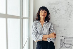 Portrait of female architect standing beside architecture drawings in office. Businesswoman standing in office with arms crossed.