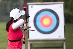 Portrait of female athlete practicing archery in stadium.