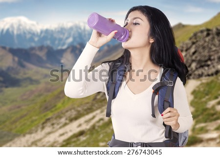 Portrait of female backpacker drinks fresh water from the bottle while carrying backpack on the edge of mountain