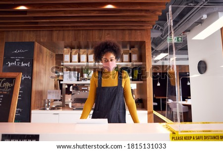 Portrait Of Female Business Owner Of Coffee Shop In Mask Behind Counter During Health Pandemic Foto stock ©