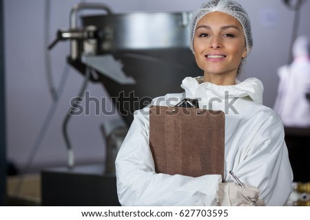 Portrait of female butcher holding clipboard at meat factory
