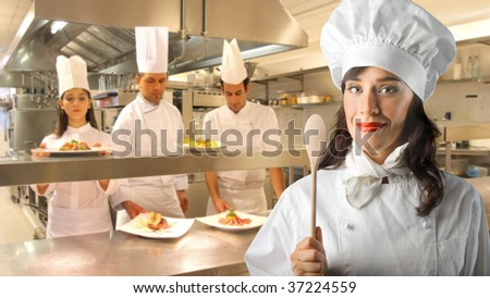 portrait of female chef and her assistants in the kitchen