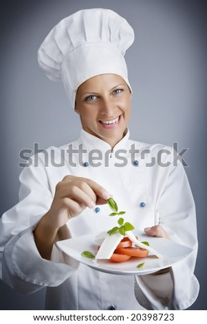 portrait of female chef, composing a cheese and tomato starter