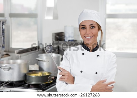 portrait of female chef looking at camera in kitchen